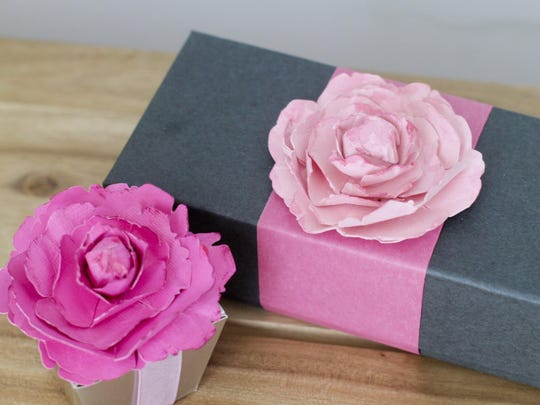 Flowers made out of cardstock used to adorn gift boxes.