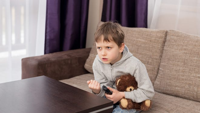 Nervous 7 year old boy child sitting on the sofa and watching tv. Hugs his favorite teddy bear and changing channels by remote control.