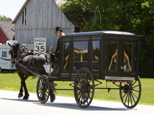 Granddaughter Brittany Raab, looks back before turning the hearse carrying the remains of her grandfather Arnold Raab, of Cascade, to Greenlawn Memorial Park Friday in Kohler.  The late Raab was a well known horse and carriage enthusiast.