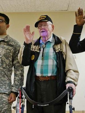 World War II veteran Sherwin Callander, 94, center, recites the Oath of Allegiance during a naturalization ceremony with Army Spc. Gulam Ali, left, originally from India, and Army Spc. Iddrisu Ibrahim, originally from Ghana, right, on Monday in Atlanta, Ga.The World War II veteran from Alabama is headed to France for D-Day ceremonies, a trip that seemed unlikely just last week.