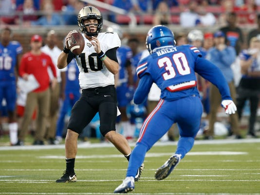 Central Florida quarterback McKenzie Milton (10) drops back to pass as SMU linebacker Shaine Hailey (30) defends during the first half of an NCAA college football game, Saturday, Nov. 4, 2017, in Dallas. (AP Photo/Mike Stone)