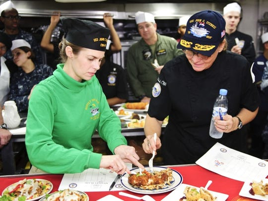 Kristen Fabry, left, judges dishes during an baking competition in the bake shop aboard the USS John C. Stennis in 2011. At the time, John C. Stennis was deployed to the U.S. 5th Fleet area of responsibility conducting maritime security operations and support missions as part of Operations Enduring Freedom and New Dawn.