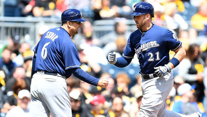 Travis Shaw of the Milwaukee Brewers celebrates his solo home run with third base coach Ed Sedar  during the fourth inning against the Pittsburgh Pirates at PNC Park.