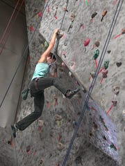 Abigail Farchione hangs on tight as she swings her legs towards new foot holds while climbing a difficult overhanging route at RockVentures in Rochester.