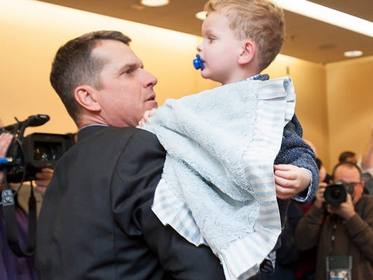 """Jim Harbaugh picks up his son Jack -- """"Mighty Jack the Quarterback"""" -- at the end of the press conference."""