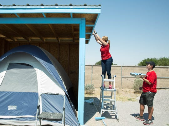 Keller Williams employee Minerva Al-Tabbaa, left, and volunteer Kaleb Judy,16, right, work to finish painting a tent shelter at Camp Hope, Thursday, June 22, 2017.