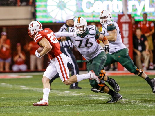 FILE - In this file photo from Sept. 20, 2014, Nebraska defensive back Nate Gerry (25) runs away from Miami offensive lineman Taylor Gadbois (76) after intercepting the ball in the second half of an NCAA college football game in Lincoln, Neb. Nebraska's Gerry is back at safety and loving it. The sophomore, who played linebacker last season, is playing at an All-Big Ten level in the secondary, with interceptions in four of the Cornhuskers' five conference games. (AP Photo/Nati Harnik, File)