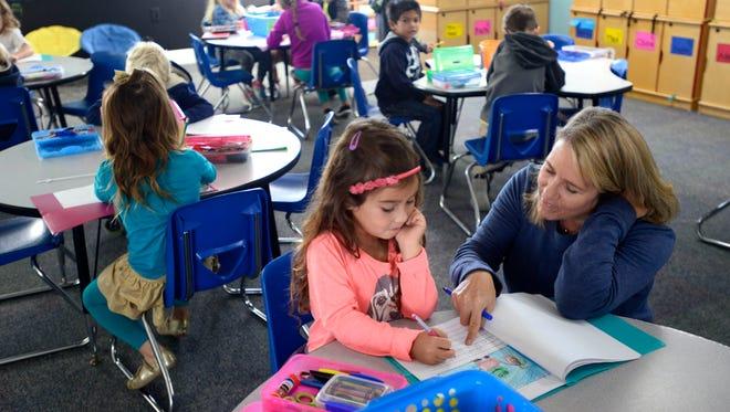Kindergarten teacher Jennifer Neal works with student Phare Newlin on Monday at Pensacola Beach Elementary School.