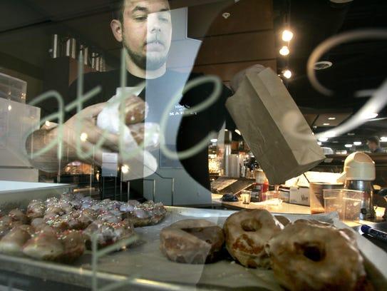 David Balmer loads glazed doughnuts into a bag for