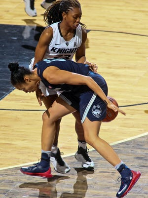 Jan 1, 2017; Orlando, FL, USA; Connecticut Huskies guard Saniya Chong (12) loses the ball to UCF Knights guard Zykira Lewis (23) in the first quarter at CFE Federal Credit Union Arena. The Connecticut Huskies won 84-48.