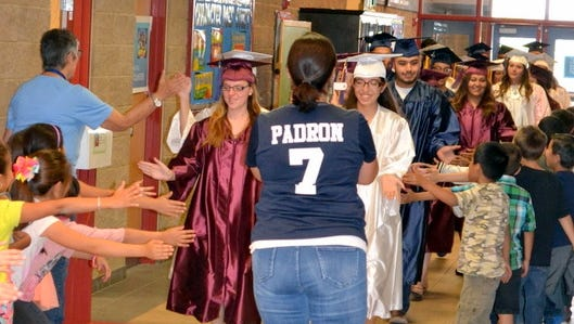 Deming High School graduating seniors receive high-fives from students as they walk through the hallways of Bataan Elementary School while Principal Marlene Padron cheers them on Friday.