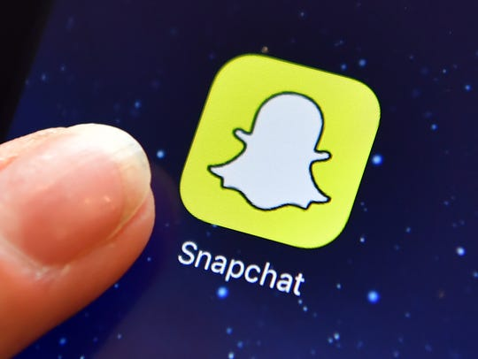 A finger is posed next to the Snapchat app logo on