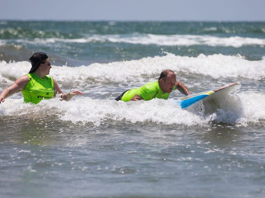 """Sylvester Barry of Austin surfs past a volunteer during """"They Will Surf Again"""" event at Horace Caldwell Pier in Port Aransas on Saturday, June 10, 2017."""
