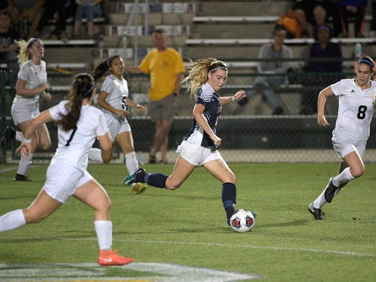 Estero's Mackenzie Gorski, center, pushes the ball up the field between Montverde Academy's Selena Salas Alonso (7) and Adriana Ordonez (8) during the first half of an Class 4A FHSAA State Soccer Championship game Friday, Feb. 23, 2018, in DeLand, Fla. (Phelan M. Ebenhack for the News-Press)