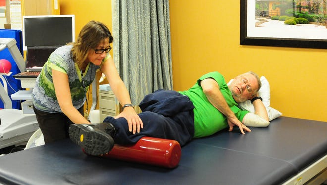 Assistant physical therapist Lynn DeWitt works with patient Rod Lough of Wrightstown earlier this month at the Department of Veterans Affairs' Milo C. Huempfner VA Outpatient Clinic in Green Bay.