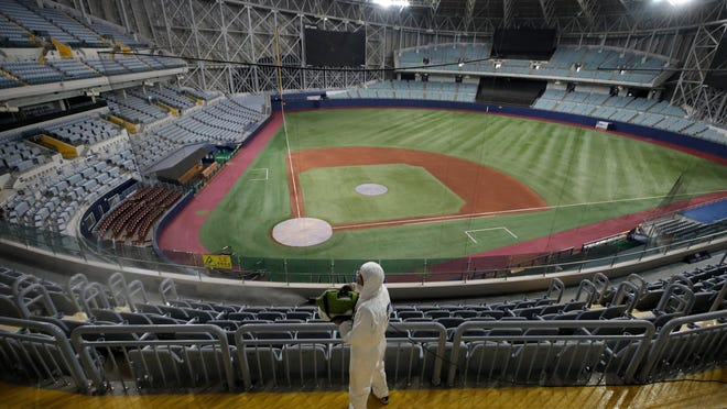 FILE - In this March 17, 2020 file photo, a worker wearing protective gears disinfects as a precaution against the new coronavirus at Gocheok Sky Dome in Seoul, South Korea. South Korea's professional baseball league said on Tuesday, June 30, it will require fans to wear masks and to sit at least a seat apart as it prepares to bring back spectators in the coming weeks amid the coronavirus pandemic.