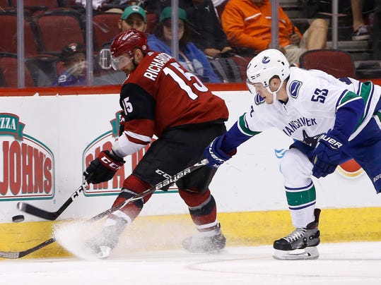 Arizona Coyotes center Brad Richardson (15) and Vancouver Canucks center Bo Horvat (53) battle for the puck during the second period of an NHL hockey team Sunday, March 11, 2018, in Glendale, Ariz. (AP Photo/Ross D. Franklin)