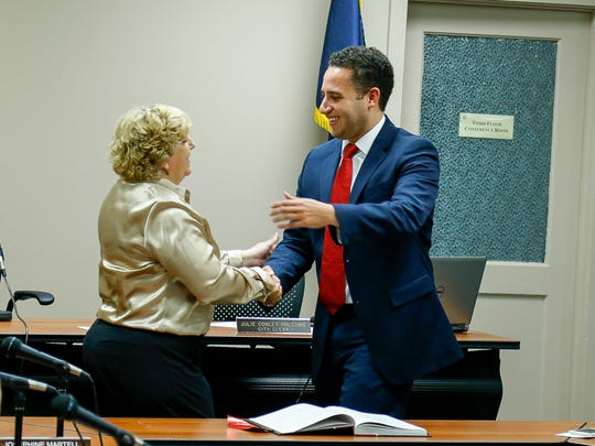 Mayor Svante Myrick shakes hands with City Clerk Julie Holcomb after being sworn in for his second term as mayor.