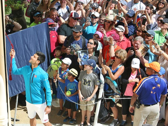 Novak Djokovic unveils a mural with his likeness at the Indian Wells Tennis Garden during the BNP Paribas Open, March 11, 2016.