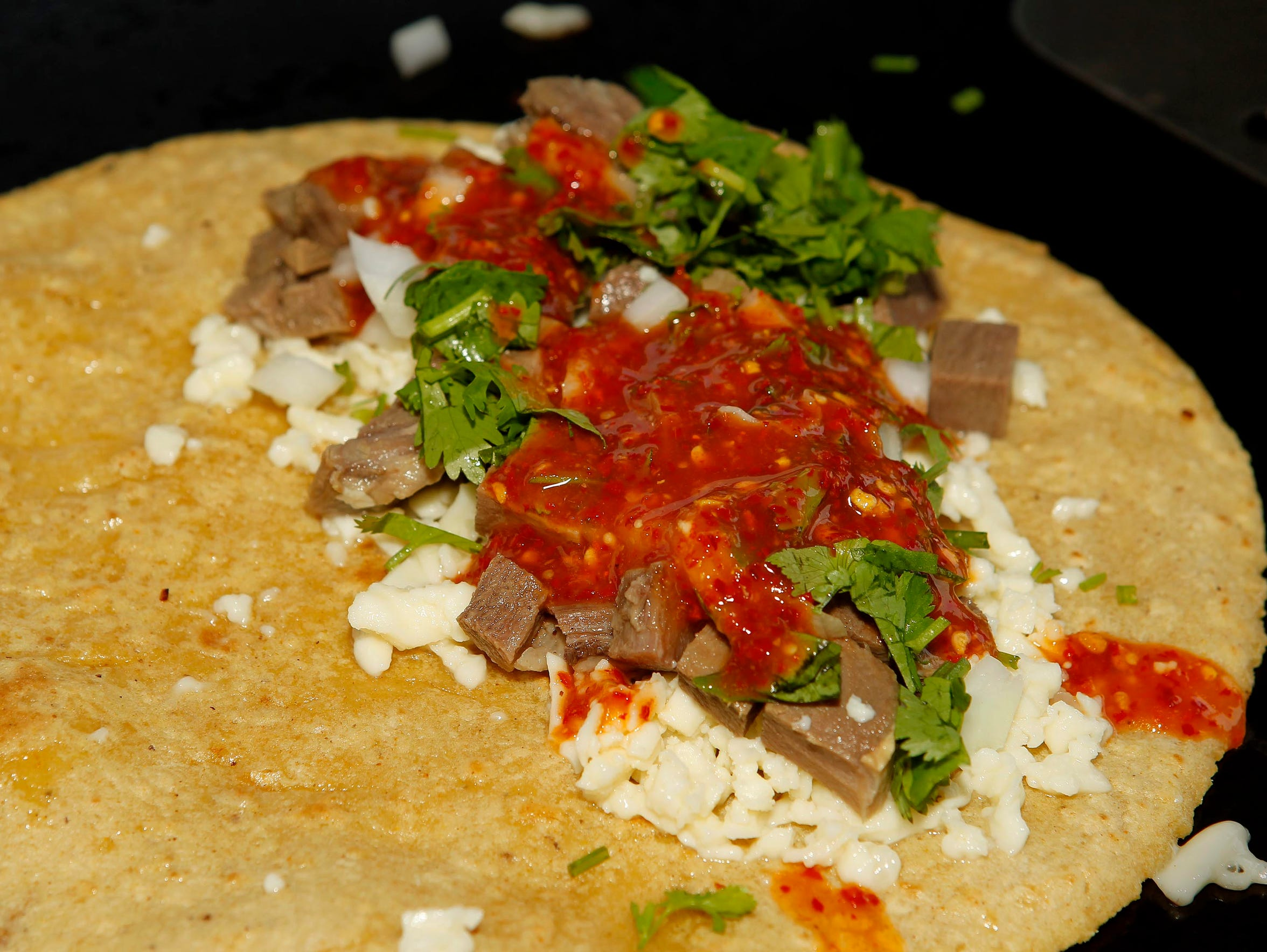Onion is sprinkled on a  quesadilla by Chilango Express,