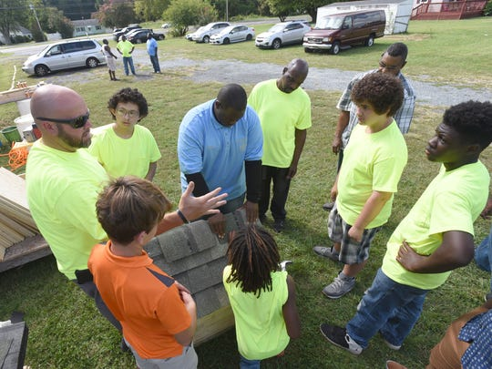 Mebers of the Young Lions listen how to put shingles on during The Young Lions Dog House build at Trinity Tabernacle Church and Comminity Center in Salisbury Sunday, Sept. 17, 2017. The youth group sponsored by Labyrinth 807 Masonic Lodge of Salisbury, were on their way to building 15 dog houses with donated material by Lowe's of Salisbury and The Roofing Center. (Photo by Todd Dudek for The Daily Times)
