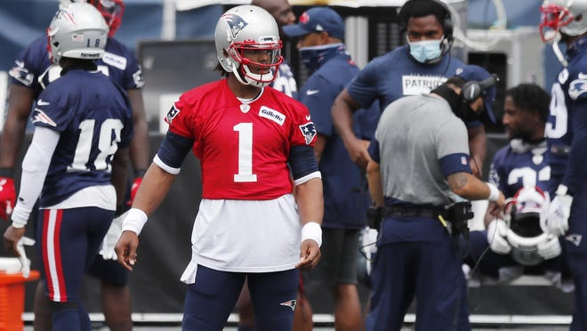 Patriots quarterback Cam Newton stands on the sideline before a training camp scrimmage gets underway Friday at Gillette Stadium.