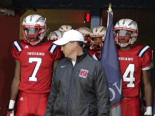 Simeon Ward (7) and Jules Rice (14) flank coach Chris Majors coming out of the tunnel Oct. 17 in their game against Williamsburg.