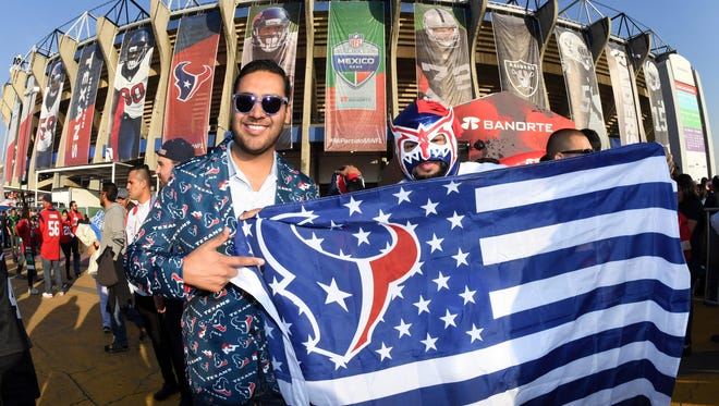 Houston Texans fans pose with a flag before an NFL game against the Oakland Raiders at Azteca Stadium in Mexico City on Nov. 21.