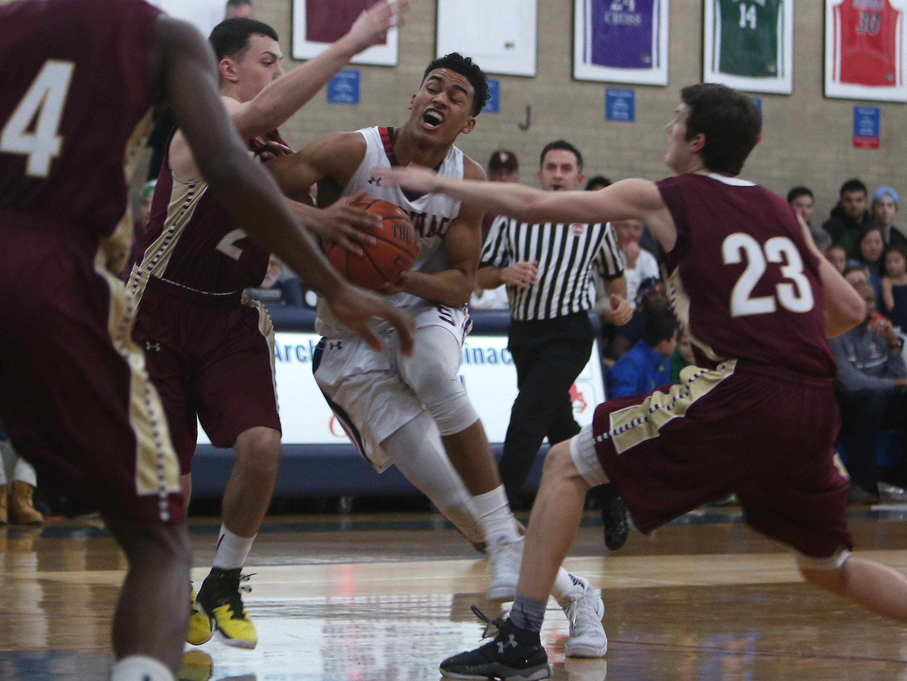 Stepinac's Jordan Tucker (5) drives to the basket while covered by Iona's Jon Brennen (2) and Patrick Flemming (23) during boys basketball action at Archbishop Stepinac High School in White Plains Jan. 8, 2016.