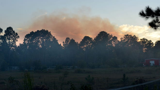 Smoke hangs over the horizon while about 80 acres burn near Garcon Point Road in 2013.