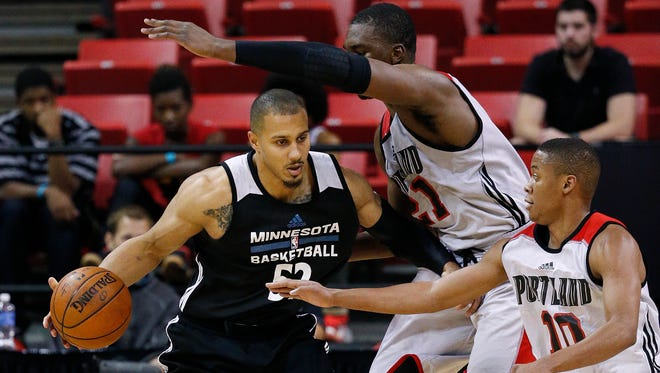 Minnesota Timberwolves' Jordan Morgan drives into Portland Trail Blazers' Noah Vonleh, center, and Tim Frazier during the second half of an NBA summer league basketball game Wednesday, July 15, 2015, in Las Vegas.