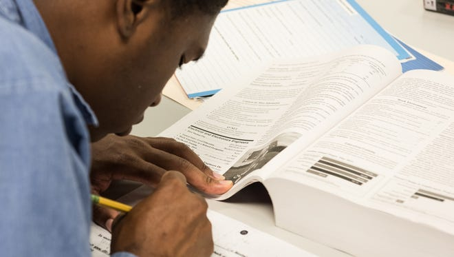 An inmate reads through a form necessary for completing enrolling in a GED certificate course at Eastern Correctional Institute in Westover on Tuesday, Sept. 16, 2016.