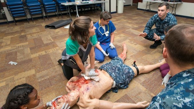 Amber Roth, of Pensacola High School, from left, Trinity Holmes, from Pine Forest High School, and Matthew Hamricks, of Tate High School, get a few pointers from corpsman David Gonzalez, right, while treating a mannequin with injuries from a motorcycle accident during the summer medical preparatory program at the Navy Hospital in Pensacola on Thursday, June 21, 2018.