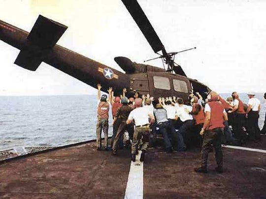 Men aboard the USS Blue Ridge push a helicopter over the side during the evacuation of Saigon, April 1975. U.S. Navy vet James Miller of Indio is to the right of the man wearing a blue shirt and blue jeans.