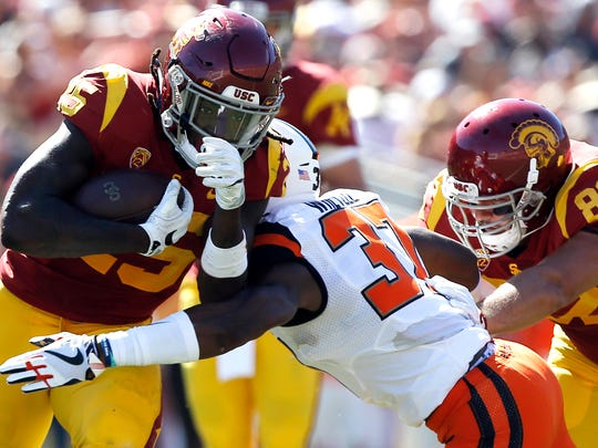 Southern California running back Ronald Jones II, left, runs through Oregon State linebacker Kee Whetzel, center, with tight end Tyler Petite, right, blocking during the first half of an NCAA college football game in Los Angeles, Saturday, Oct. 7, 2017. (AP Photo/Alex Gallardo)
