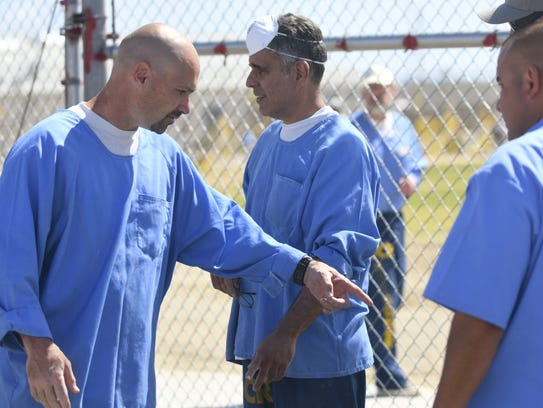 Ed Harvey, 46, works with fellow inmates to install