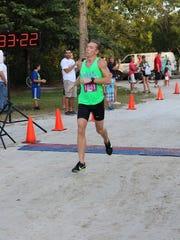 Male winner Ryan Stafford crosses the finish line at