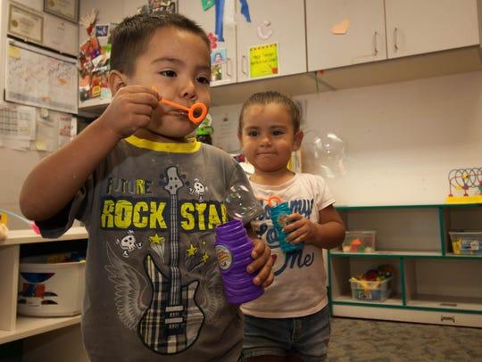 Jayden Chavez, left, 2, and Dayan Chavez, 2, blow bubbles