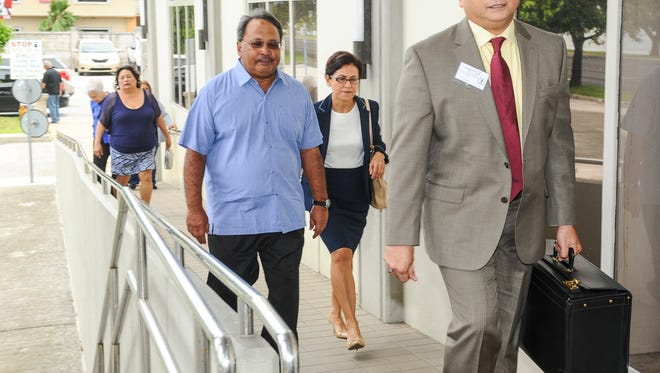 Airport consultant Francisco Roberto Santos, center, prepares to enter the U.S. District Court of Guam with his attorney, Jay Arriola, right, on Thursday, Oct. 15.