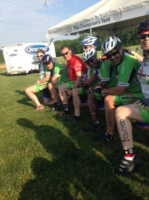 """Members of Shore Velocity have """"Bob"""" written on their legs to honor their injured president, Bob Maddux, at the Tour de Cure in Easton on Saturday."""