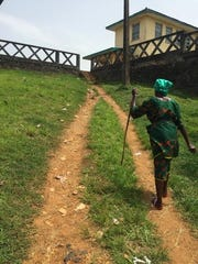 A woman walks uphill to the J.J. Dossen Hospital in Harper, Liberia. Dr. Mead worked at the facility.
