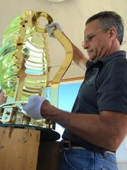 Dan Spinella, of Artworks Florida, installs the fifth-order replica Fresnel lens at the historical Port Clinton Lighthouse.