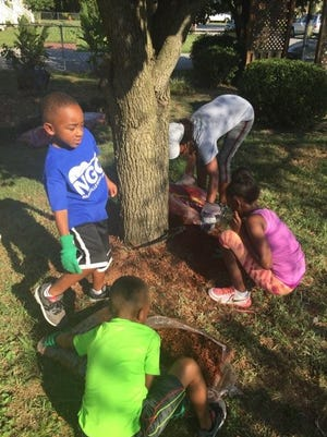A group of young volunteers landscape the property at the FRC Guesthouse, where out-of-town family members can stay for free while visiting incarcerated family members in Nashville.