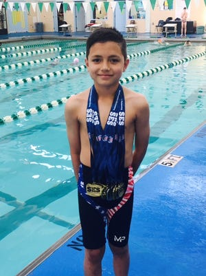 Eight-year-old Landon Garcia poses with all the medals he won in competing for the Greater Pensacola Aquatic Club youth team at the recent Southeastern Swimmer Region IV Championships.