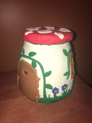 Courtney used clay on top of a glass jar to create this mushroom fairy house.