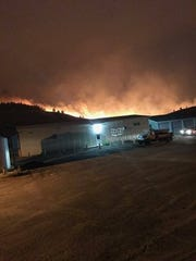The Alice Creek fire crests the ridge and moves toward a Montana Department of Transportation shop early Sunday.
