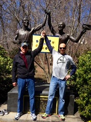 Ed Sponseller, left, and his son Steve Sponseller, right, hold hands in front of a statue of Johnny Kelley at the Boston Marathon.