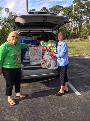 "Barbara Pray, left, Holy Family Catholic Church ""Back To Basics Angels"" chairwoman, and Carol Inzirillo, president of the Holy Family Council of Catholic Women, pack gift bags into Pray's car."