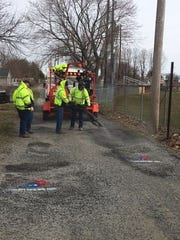 Crew repairing potholes in Milford on behalf of Domino's.