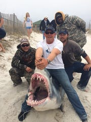 Earnie Polk, center, Kenny Petersen, left, Joey Polk, right and Adam Madison are seen with a 10-foot-6-inch mako shark Kenny caught off Navarre Beach.